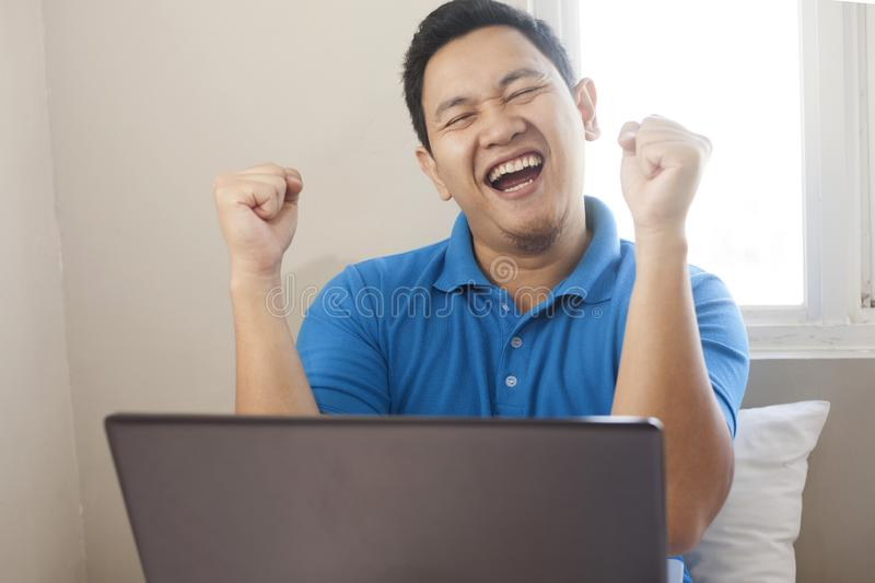 Successful Man Celebrating Victory, Entrepreneur Working Online Business From Home. Portrait of young Asian man celebrating victory while looking at laptop royalty free stock photo