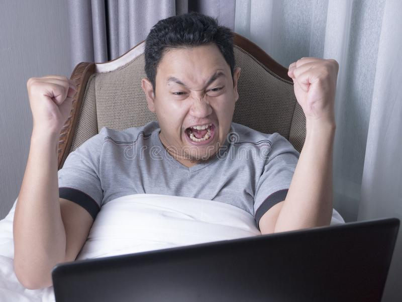 Successful Man Celebrating Victory, Entrepreneur Working Online Business From Home. Portrait of young Asian man celebrating victory while looking at laptop stock images