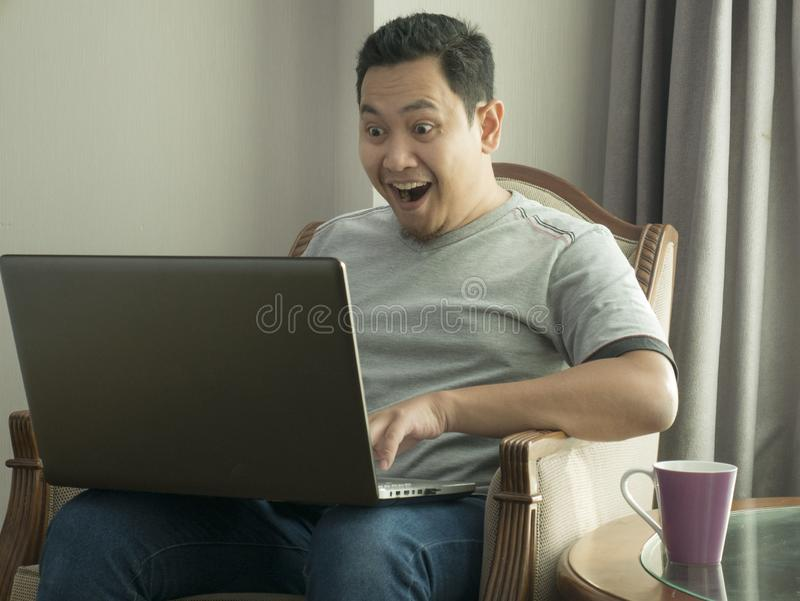 Successful Man Celebrating Victory, Entrepreneur Working Online Business From Home. Portrait of young Asian man celebrating victory while looking at laptop royalty free stock photos