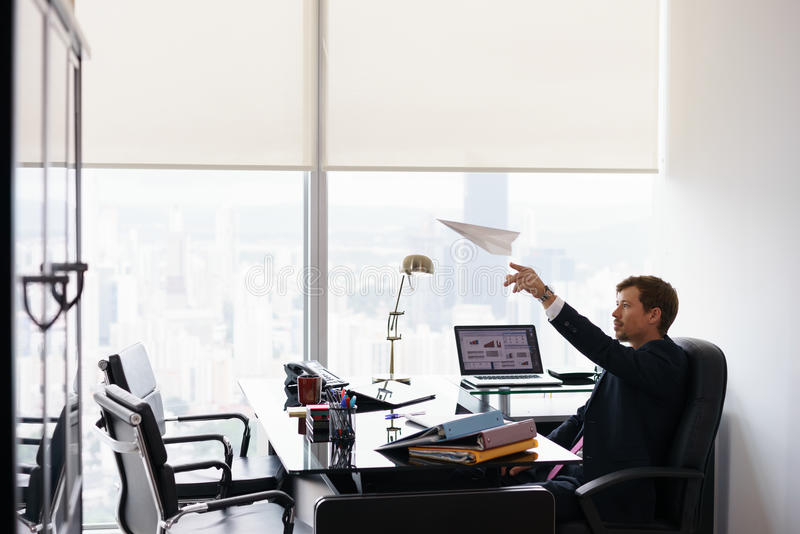 Successful Man Office Worker Daydreaming Throwing Paper Airplane. Corporate manager in modern office takes a break and prepares a paper airplane. The bored man stock image