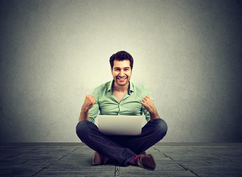 Successful man rejoices while using a laptop stock photos