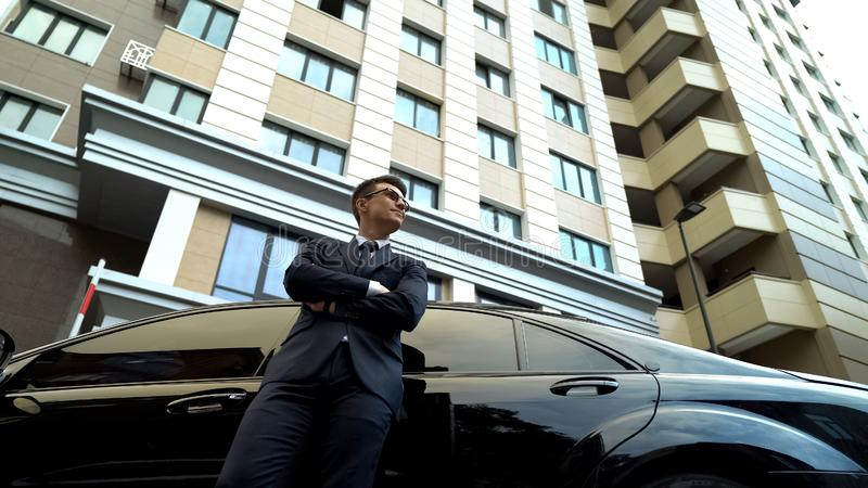 Successful man standing near luxury car against condominium complex, mortgage. Stock photo royalty free stock images