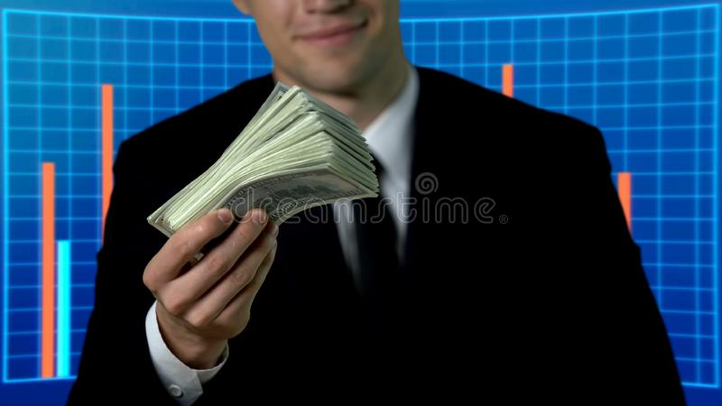 Successful man in suit showing bunch of dollars, business charts on background. Stock photo royalty free stock image