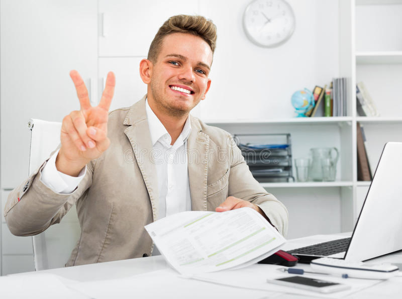 Successful man working showing victory gesture. Successful young man working with laptop and showing victory gesture stock photo