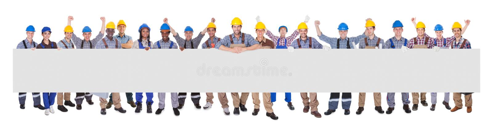 Successful manual workers with blank billboard royalty free stock image