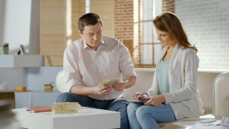 Successful married couple counting cash at home, family budget money, savings stock photo