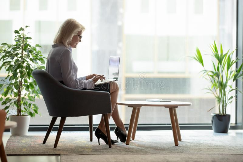 Successful mature businesswoman using laptop near big window royalty free stock photography