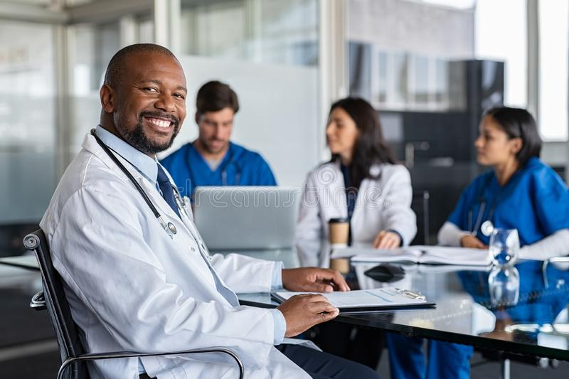 Successful mature doctor at hospital meeting royalty free stock photo