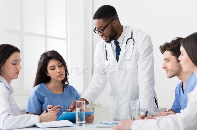 Successful Medical Team Discussing Diagnosis At Conference stock photo