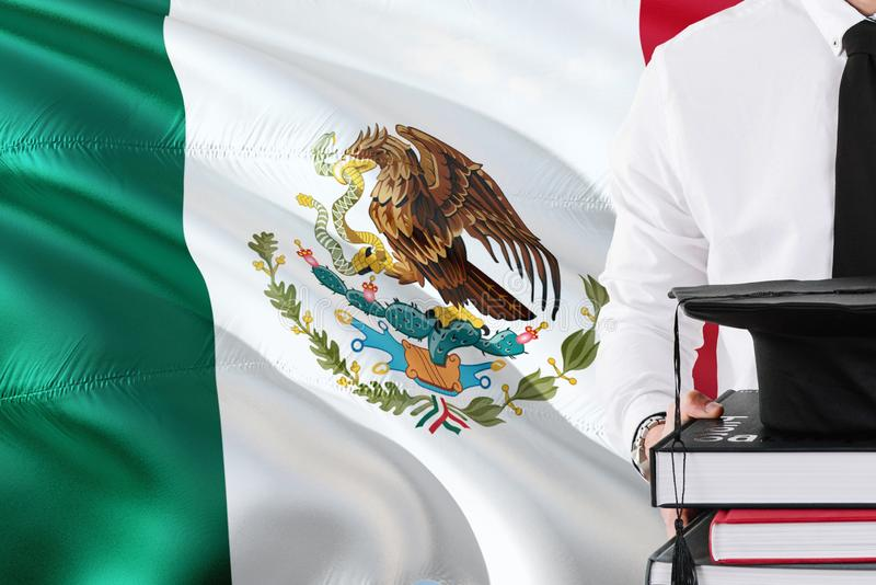 Successful Mexican student education concept. Holding books and graduation cap over Mexico flag background stock image