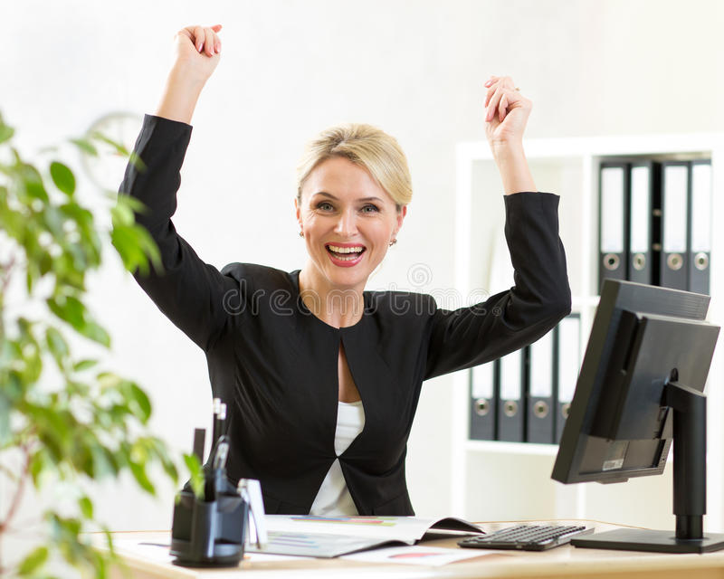 Successful middle-aged business woman holding arms up sitting at pc in office royalty free stock photos