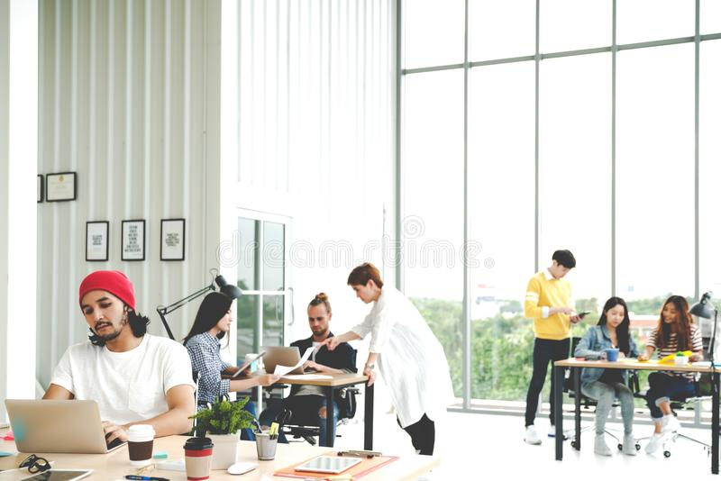 Successful multiethnic business team in routine work creative lifestyle standing, sitting and talking together at modern office wi stock photo