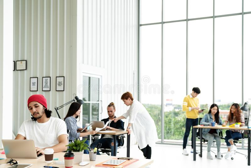 Successful multiethnic business team in routine work creative lifestyle standing, sitting and talking together at modern office. With wide angle view. Young stock image