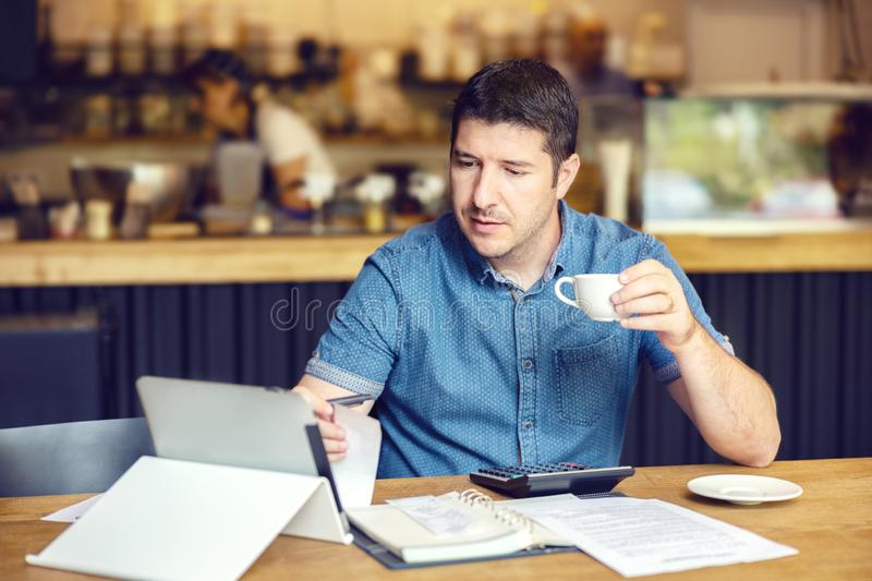 Successful new small business restaurant owner calculating bills taxes and expenses of his small business royalty free stock photography