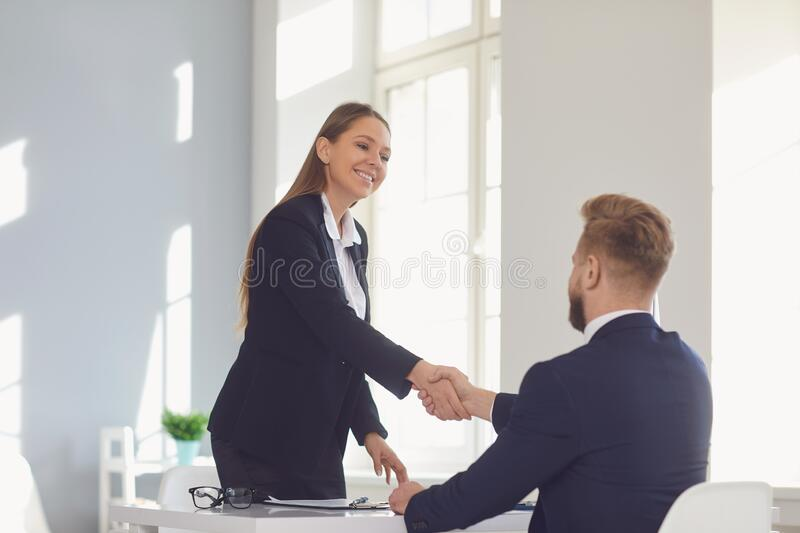Successful office interview. The conclusion of the contract. Businessman and businesswoman handshake at the table after royalty free stock images