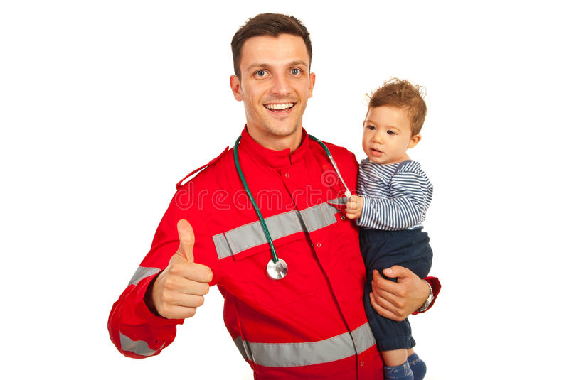 Successful paramedic with baby. Successful paramedic give thumb up and holding baby boy isolated on white background stock photo