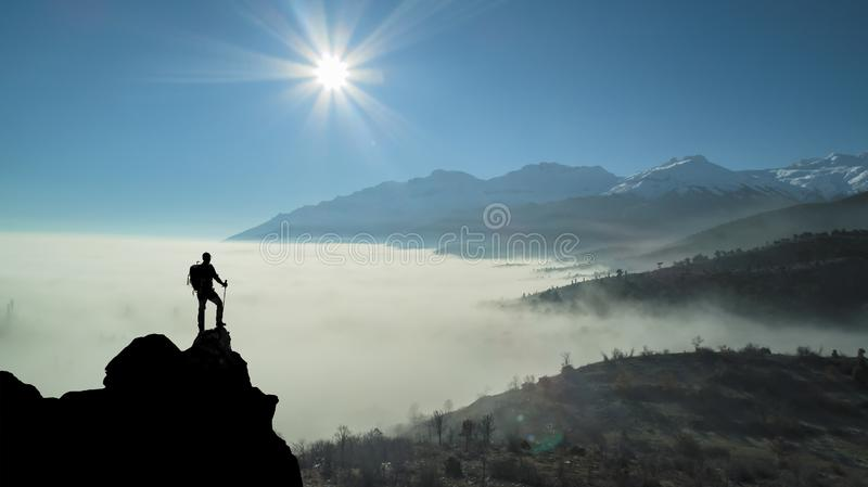 Successful peak discovery on a spectacular mysterious day. Views of the fog clouds and the discovery adventure of the top climber royalty free stock photography