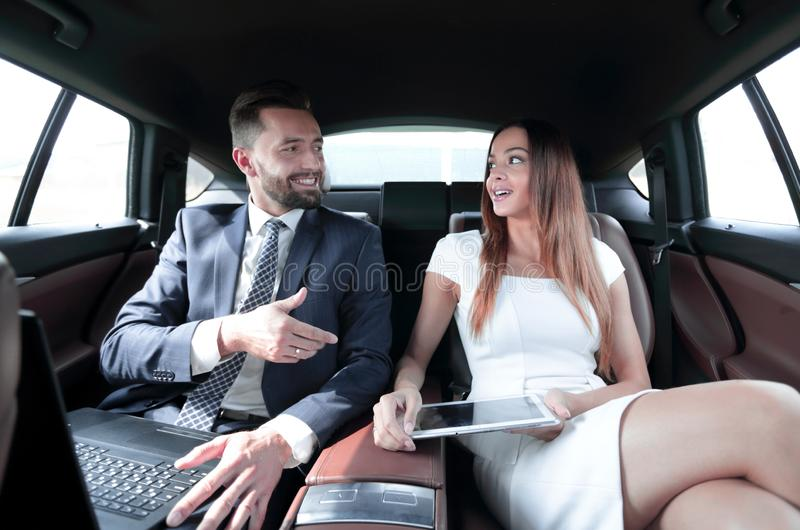 Successful people working together in back seat of car. Businesswoman and men sitting in the backseat of a car during a business trip royalty free stock images