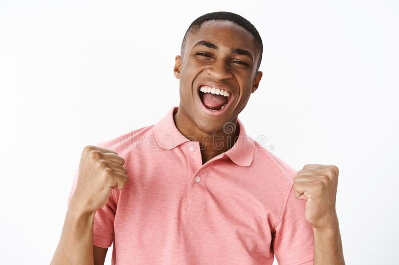 Successful pleased and happy handsome young african american guy in pink shirt clenching fists in victory and cheer stock image