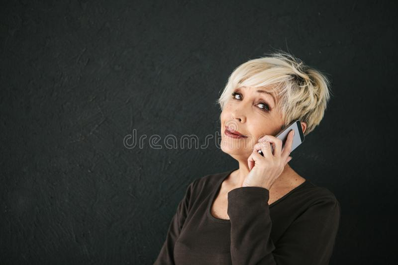 A successful positive elderly female consultant is negotiating a cell phone. Communication between people using modern stock image