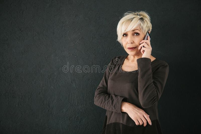 A successful positive elderly female consultant is negotiating a cell phone. Communication between people using modern stock photography
