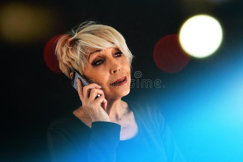 A successful positive elderly female consultant is negotiating a cell phone. Communication between people using modern royalty free stock images