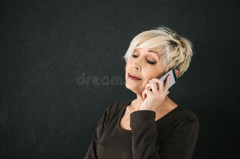 Mature beautiful positive woman talking on cell phone. A successful positive elderly female consultant is negotiating a cell phone. Communication between people stock photography