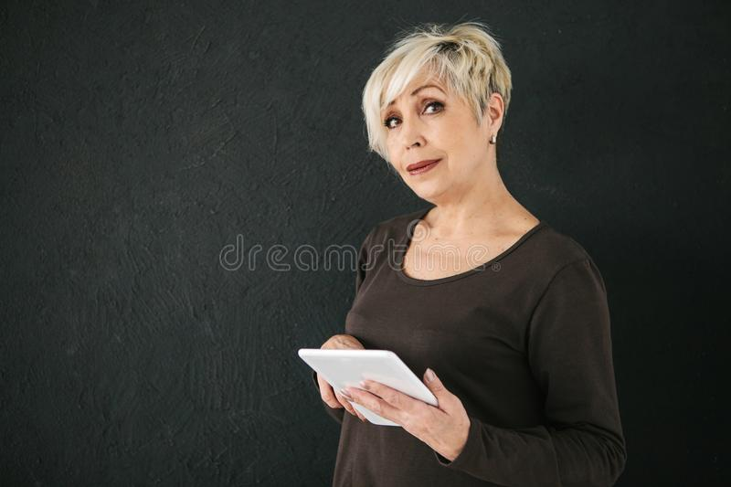 A successful positive modern elderly woman holds a tablet in her hands and uses it. The older generation and modern stock images