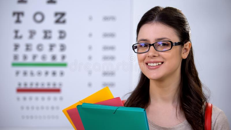 Successful pretty female ophthalmologist student in glasses smiling at camera stock images