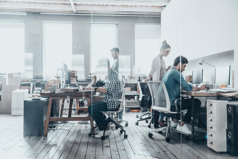 Successful professionals. Group of business people using computers and communicating while working behind the glass wall in the creative office stock image