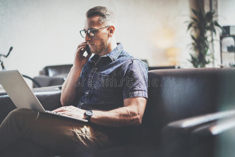 Successful Risk Manager working Laptop modern Interior Design Loft Office.Man work Vintage Sofa,Using contemporary. Smartphone Hand Calling.Blurred Background stock image