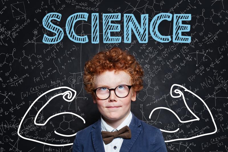 Successful school boy with ginger hair on science background. Learn science and science power concept.  stock photo