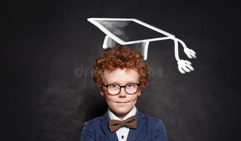 Successful schoolboy in glasses and graduation hat portrait stock photography