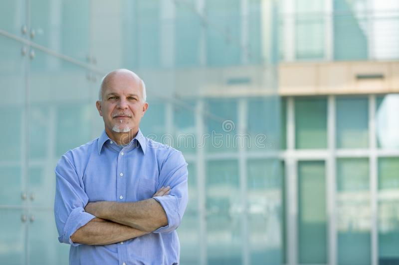 Successful senior businessman or entrepreneur. Standing with folded arms in front of modern glass windows on a commercial building with copy space royalty free stock photography
