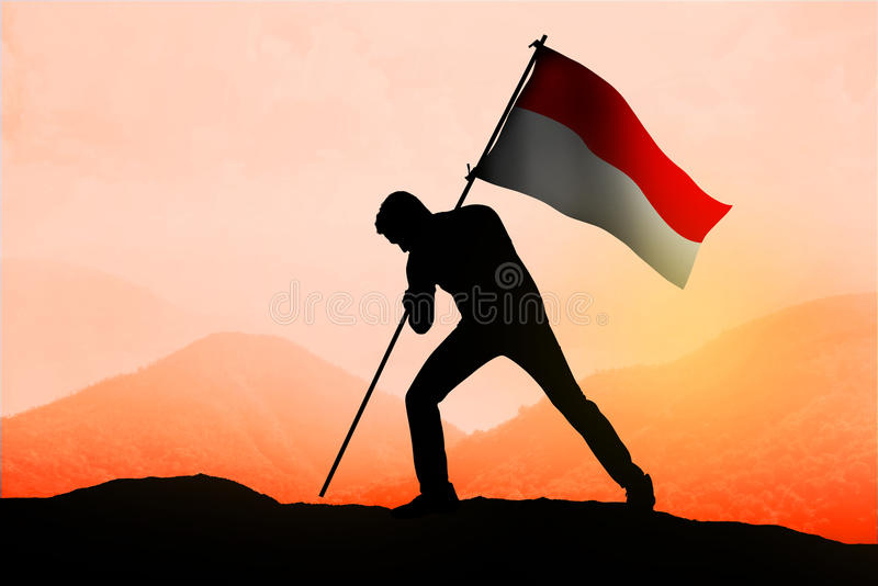 Successful silhouette man waving Indonesian flag on the mountain stock images