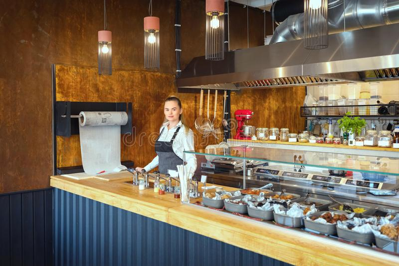 Successful small business owner woman standing behind counter of newly opened restaurant stock image