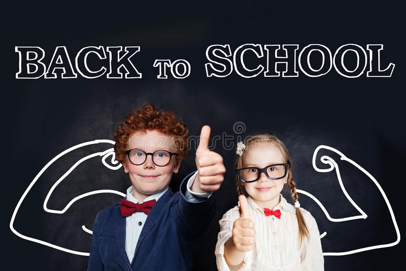 Successful smart kids in school uniform having fun on blackboard background, back to school and brain power concept royalty free stock photo