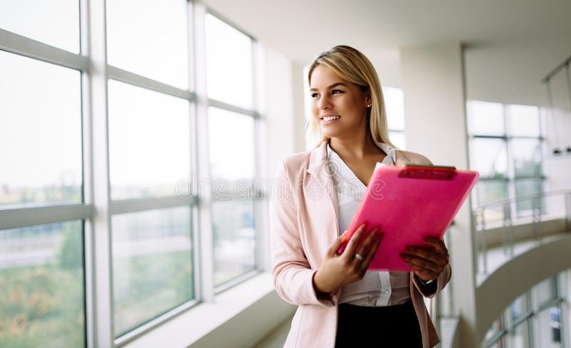 Successful smiling business woman at work holding documents, standing near window in office royalty free stock photos