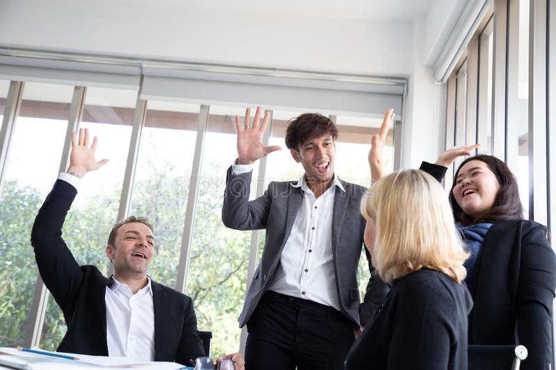 Successful startup entrepreneurs and business people team achieving goals celebrating giving high five in office. royalty free stock photography