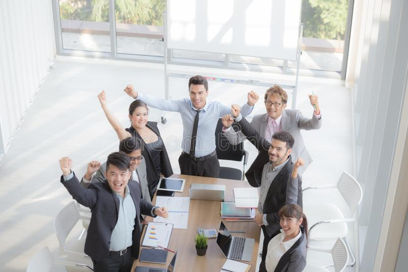 Successful startup entrepreneurs and business people team achieving goals celebrating a triumph with arms up royalty free stock photo