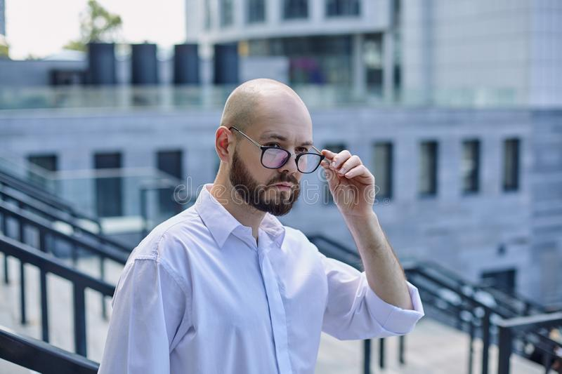 Successful strong man with a dark beard in white shirt is holding the glasses by hand royalty free stock photos