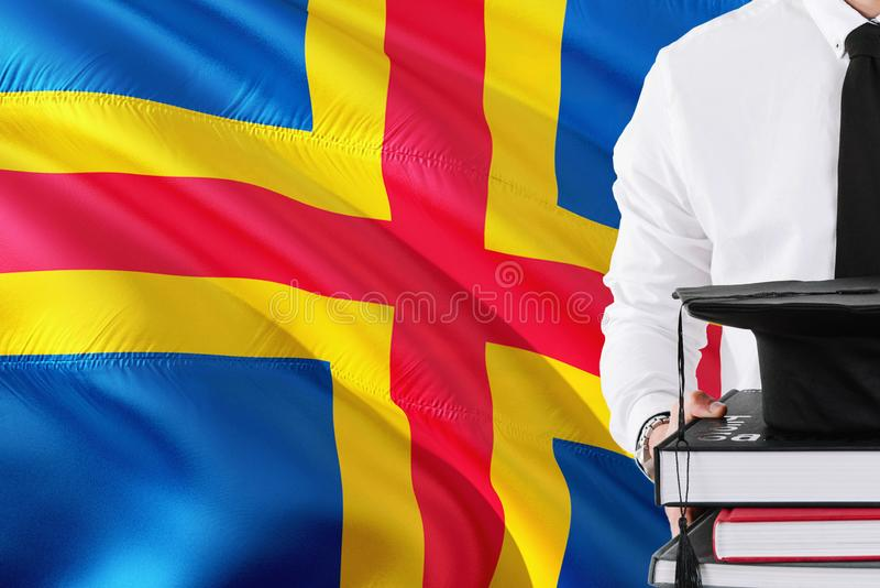 Successful student education concept. Holding books and graduation cap over Aland Islands flag background.  stock photography