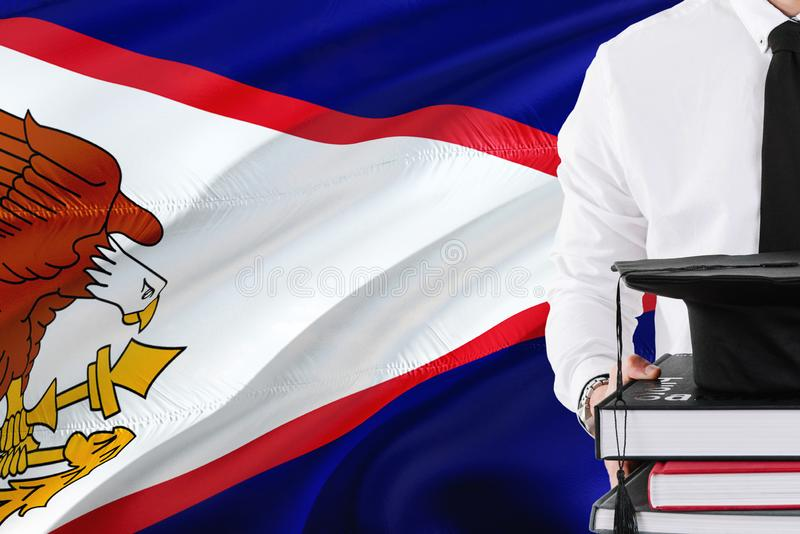 Successful student education concept. Holding books and graduation cap over American Samoa flag background stock photography