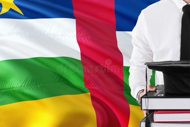 Successful student education concept. Holding books and graduation cap over Central African Republic flag background royalty free stock photo