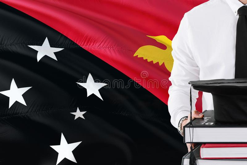 Successful student education concept. Holding books and graduation cap over Papua New Guinea flag background.  royalty free stock photo