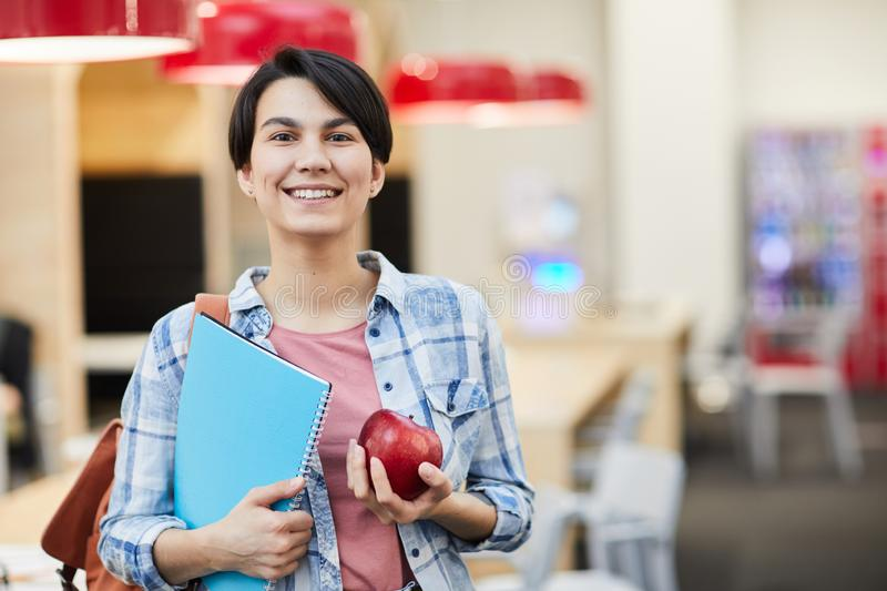 Successful student girl with apple. Portrait of confident successful student girl with short black hair standing in university room and holding apple and royalty free stock photos