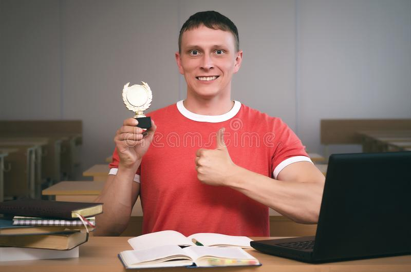 Student. Successful student graduate with golden medal trophy in his hand is sitting by school desk. Winner of school olympiad royalty free stock photos