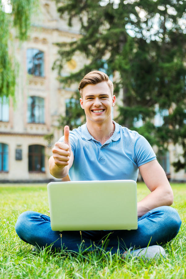 Successful student. Happy young man looking at camera and showing his thumb up while sitting on the grass with laptop royalty free stock photo