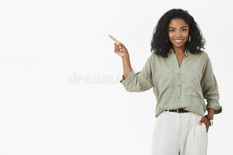 Successful stylish and happy dark-skinned businesswoman presenting project near chard holding hand in pocket pointing royalty free stock photography