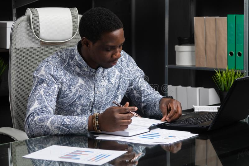 Young black businessman working with documents and laptop in office. Successful successful African top Manager of official shirt works with notebook and laptop stock photos